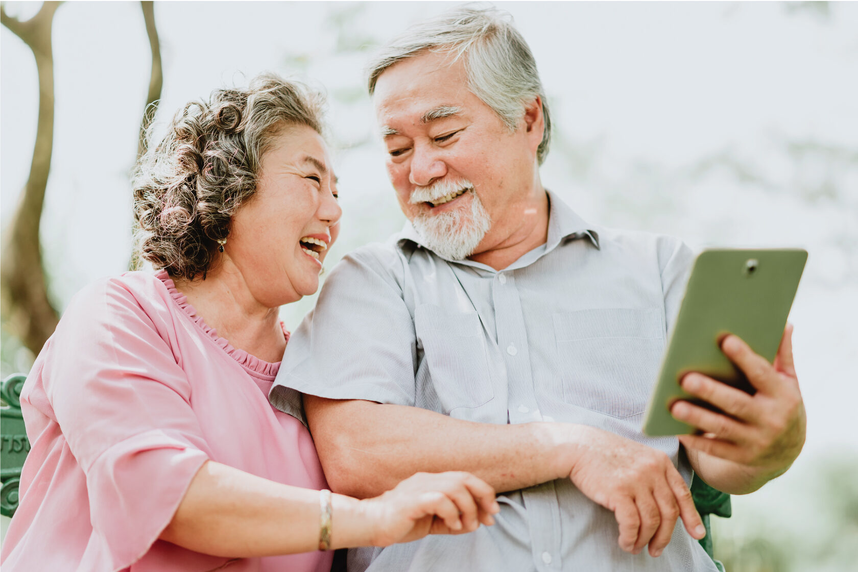 senior couple look at each other tablet on his hand