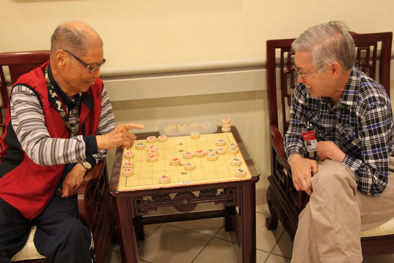 Volunteer playing chess with a senior resident