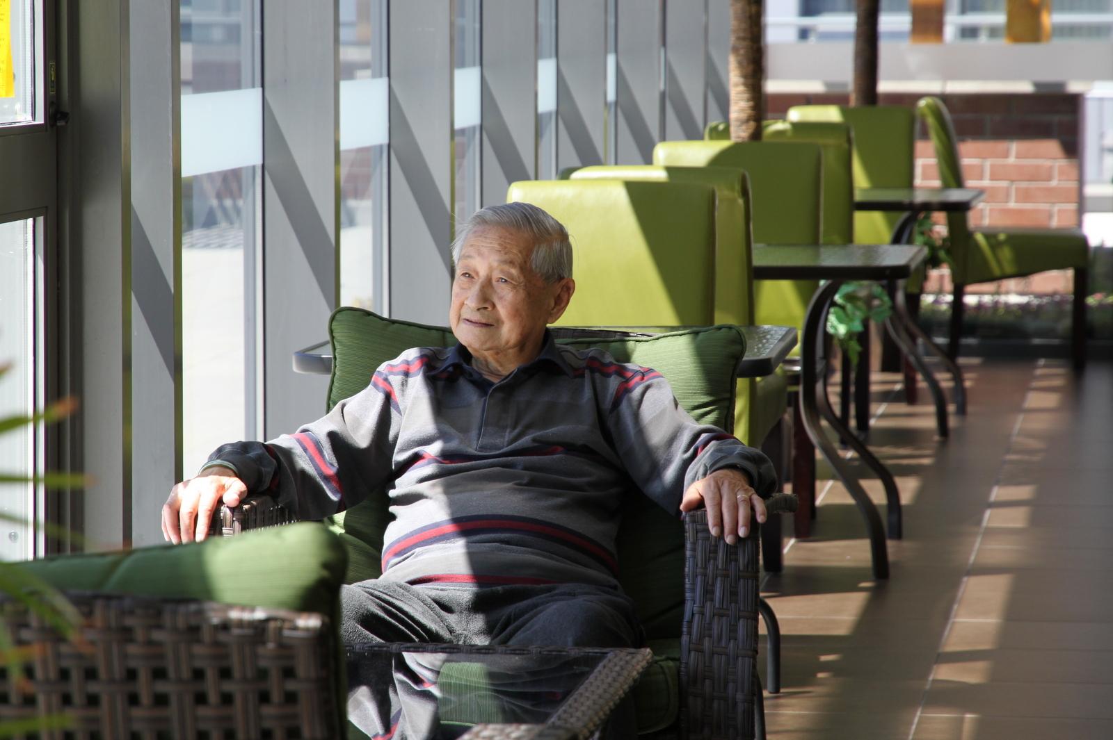 Senior sitting at Green Room at Mon Sheong Court