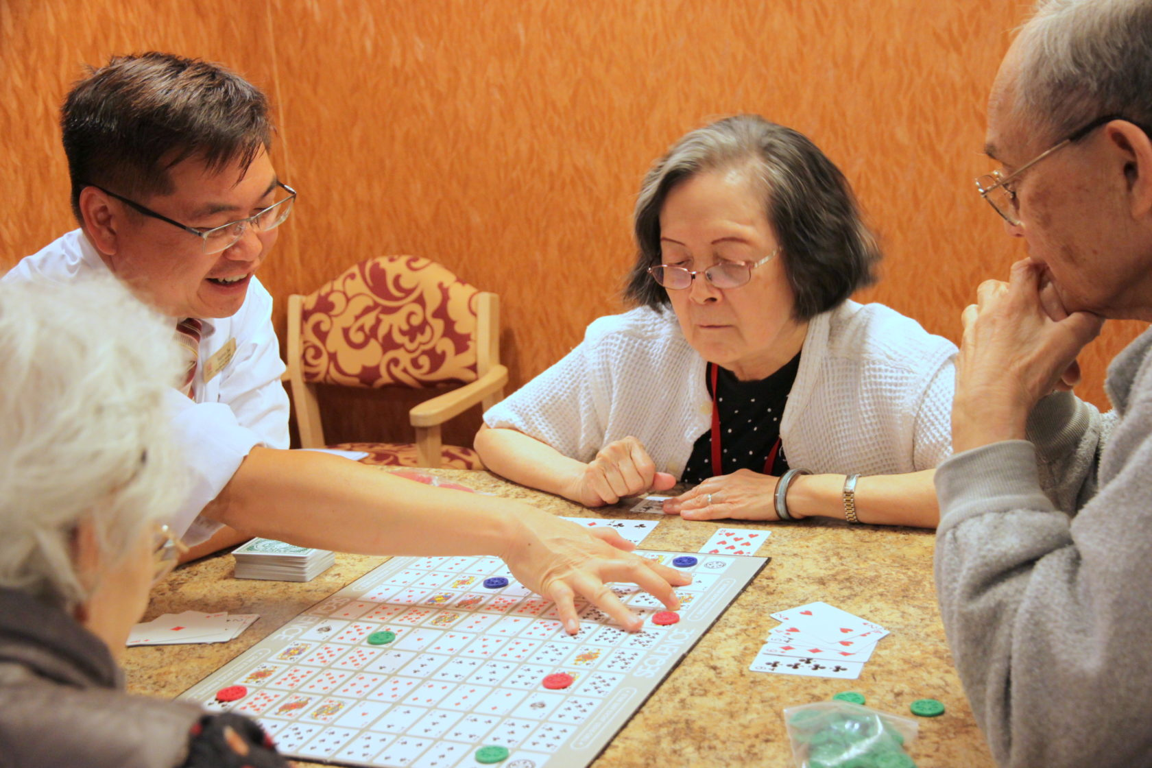 Private Care residents are playing board game together