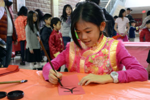 Girl writing Chinese Character