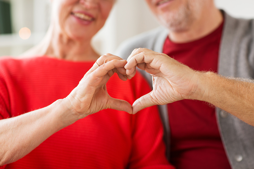 two seniors with heart shape by hands