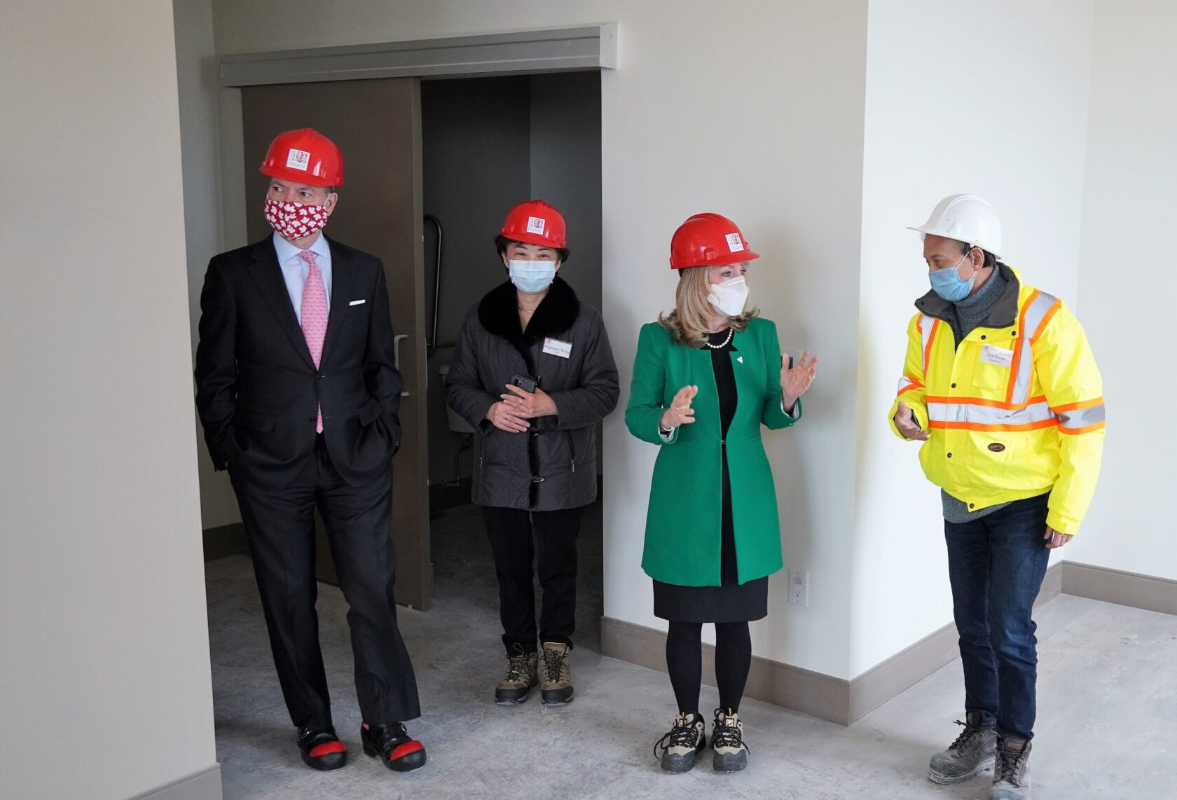 four people wearing helmet at a room